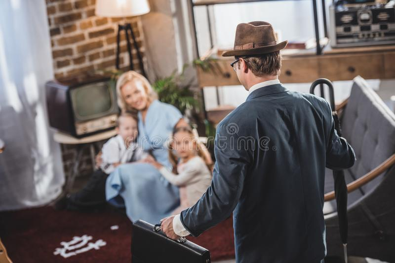 Selective focus of mother with two kids playing together and looking at father coming home. 1950s style royalty free stock photos