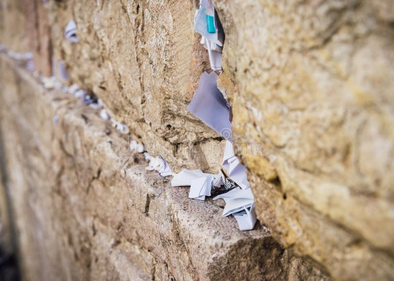 Selective focus on notes to God in the cracks between the bricks of the Western Wall, also known as Kotel, in the old stock photos