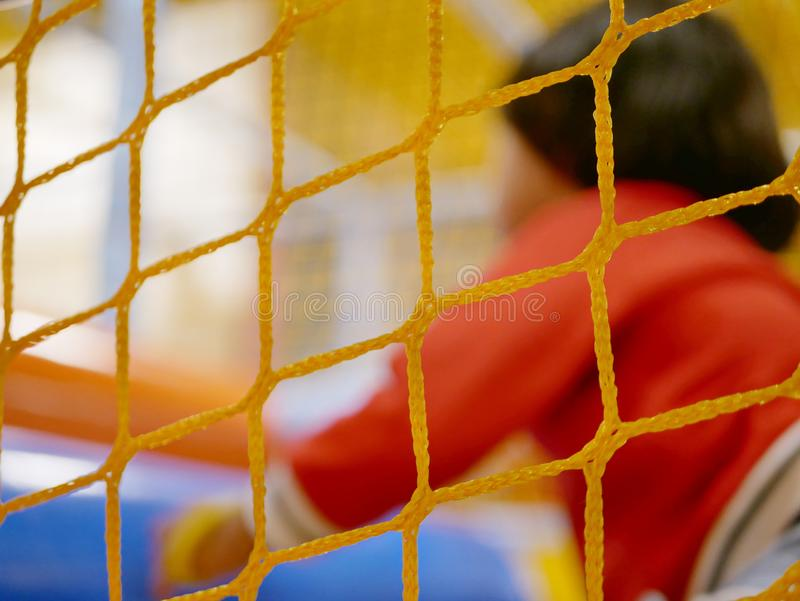 Selective focus of nylon net at an indoor childdren playground to help preventing little kids from falling out of the area, while. Selective focus of nylon net stock photos