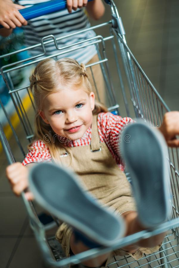 Free Selective Focus Of Little Girl Sitting In Shopping Cart Stock Photo - 129169590