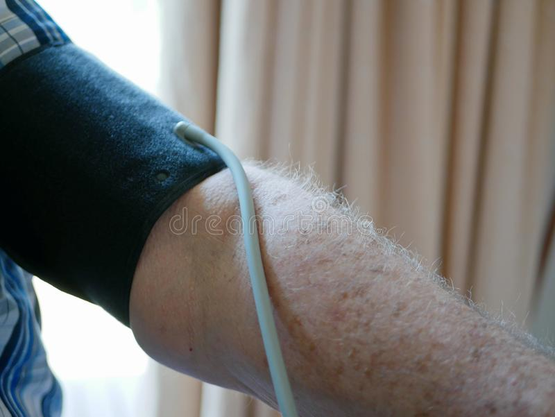 An old man`s arm with a pressure cuff on checking his blood pressure at home by himself stock photo