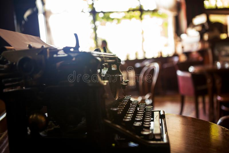 Selective focus on an old 19th-type black typewriter on a desk in a news agency`s office. Copy space stock images