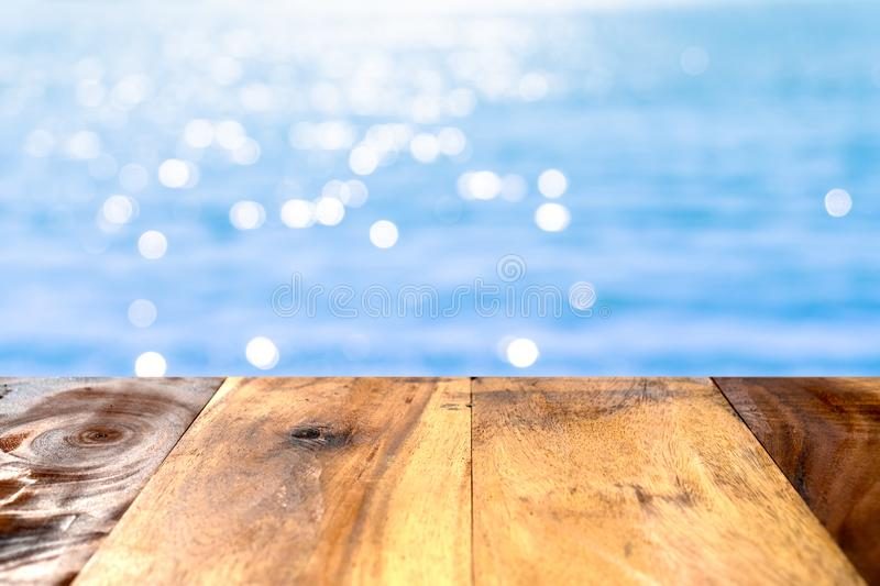 Selective focus of old wood table with beautiful beach background for display your product stock image