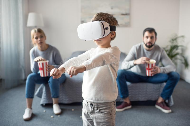 selective focus of parents with popcorn looking at kid playing in vr headset royalty free stock photography