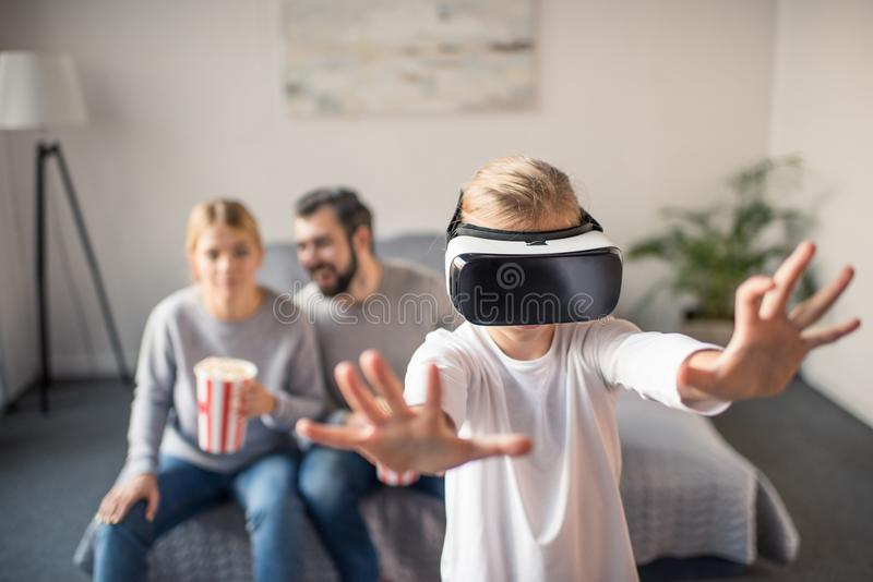 selective focus of parents with popcorn looking at kid playing in vr headset royalty free stock photo