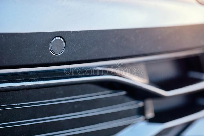 Selective focus on parking sensor of parking assistent system at front of luxurious car bumper close up on light blurred royalty free stock photo