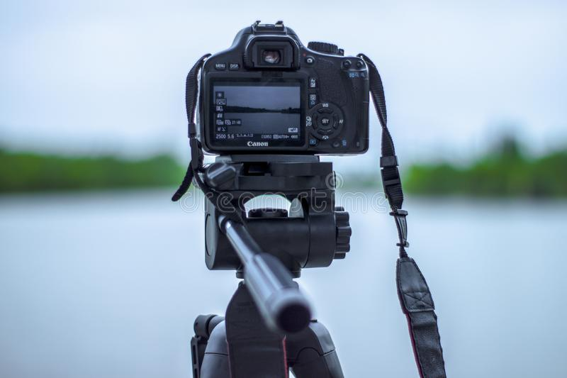 Selective Focus Photo of Black Canon Camera on Tripod Stand in Front of Body of Water Photo royalty free stock image