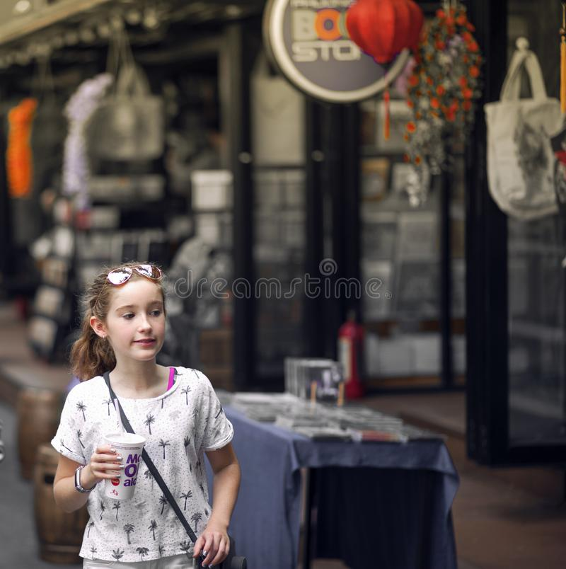 Selective Focus Photo of Girl Wearing Gray and Black Tree Print Holding Mcdonald Plastic Cup royalty free stock image