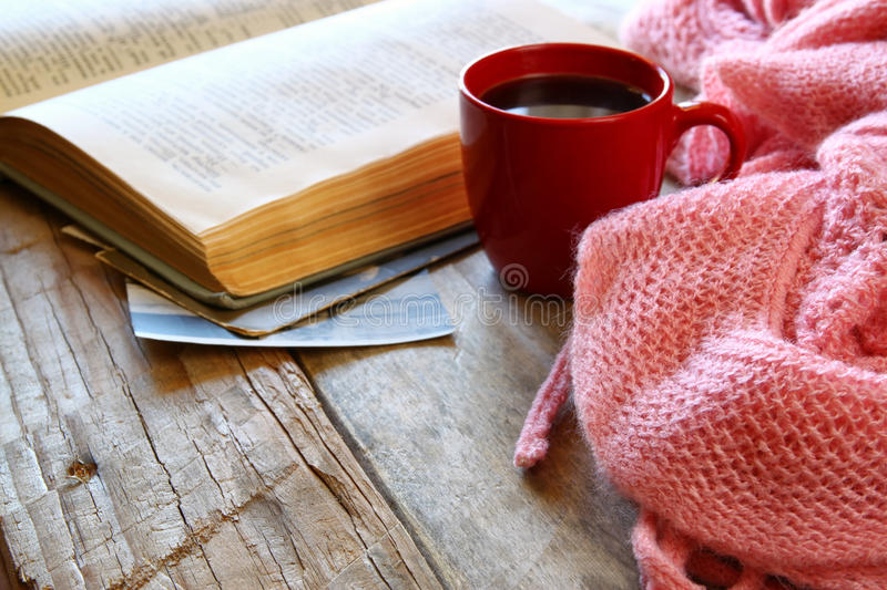 Selective focus photo of pink cozy knitted scarf with to cup of coffee, wool yarn balls and open book on a wooden table stock images