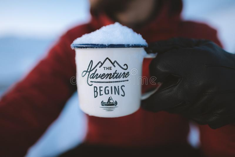 Selective Focus Photography of Person Holding the Adventure Begins Mug royalty free stock image