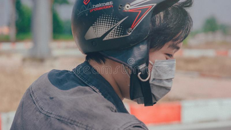 Selective Focus Photography of Person Wearing Black and Red Helmet and Gray Mask stock photo