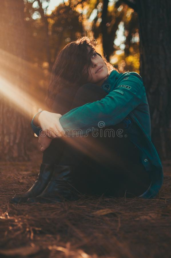 Selective Focus Photography of Woman in Green Jacket and Black Pants Sitting on Field Surrounded With Trees royalty free stock images