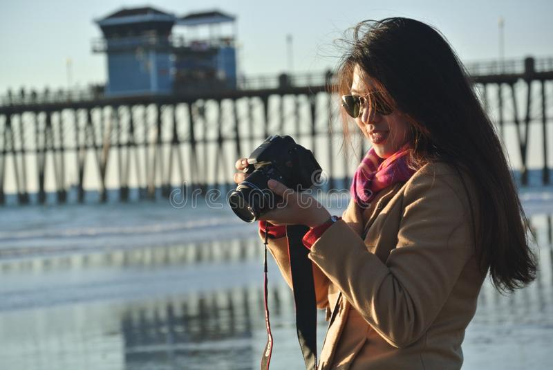 Selective Focus Photography of Woman Holding Her Camera Near Seashore stock photography