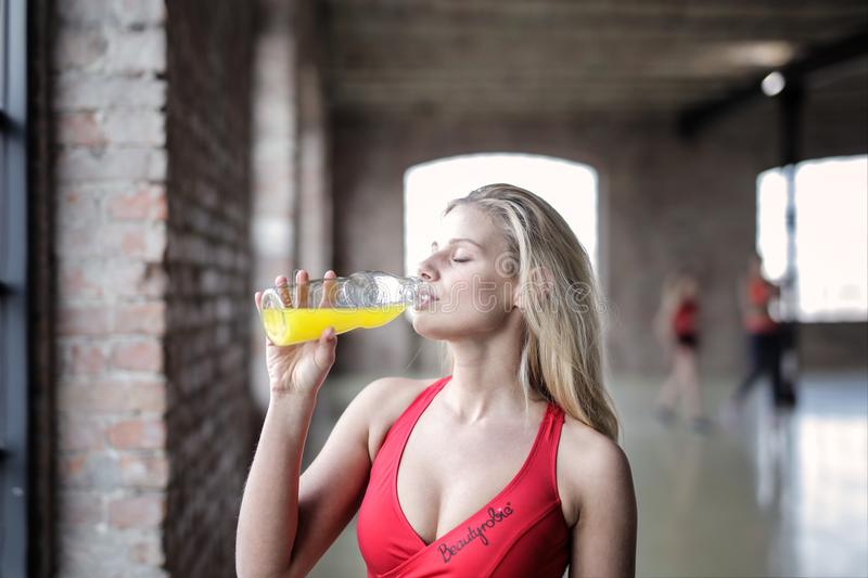 Selective Focus Photography of Woman in Red Tank Top Drinking stock image