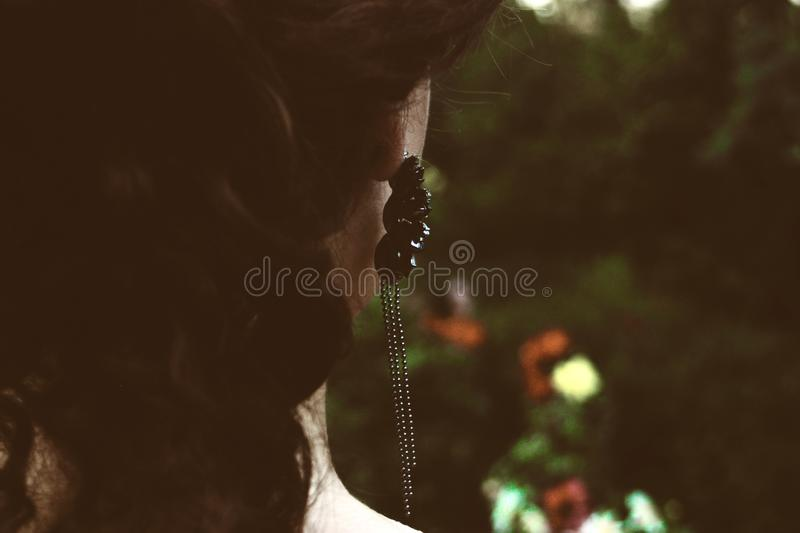 Selective Focus Photography of Woman's Back With Black Pendant Earrings stock photo