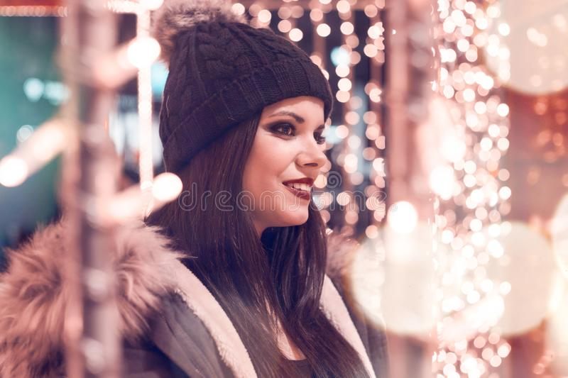 Selective Focus Photography of Woman Wearing Black Cap and Gray Parka Jacket Surrounded by Lights stock image
