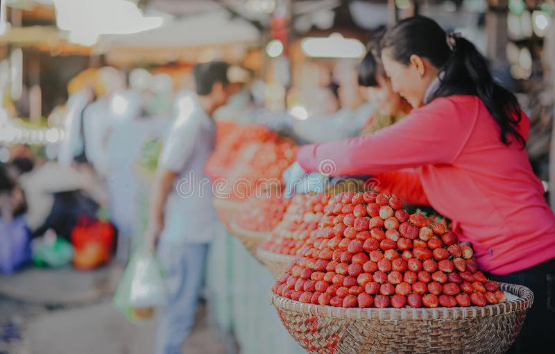 Selective Focus Photography Of Woman Wearing Red Hoodie Standing Behind Of Basket Full Of Fruits royalty free stock images