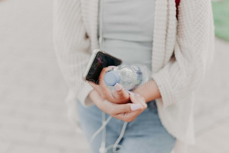 Selective Focus Photography of Woman in White Cardigan Holding Water Bottle and Black Smartphone stock photo