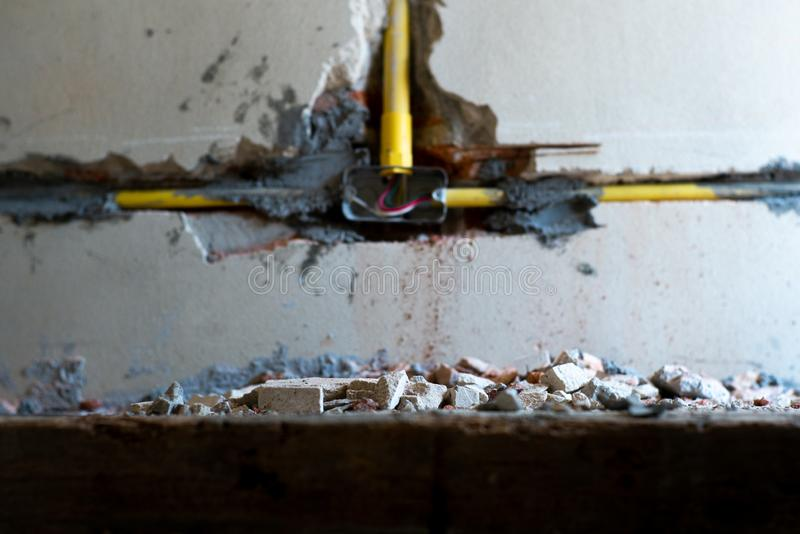 Selective focus picture of crushed concrete lump with blurred broken plastered cement wall in background. At the house under construction stock photography