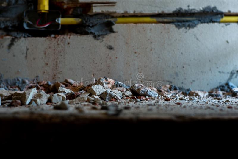 Selective focus picture of crushed concrete lump with blurred broken plastered cement wall in background. At the house under construction royalty free stock photo