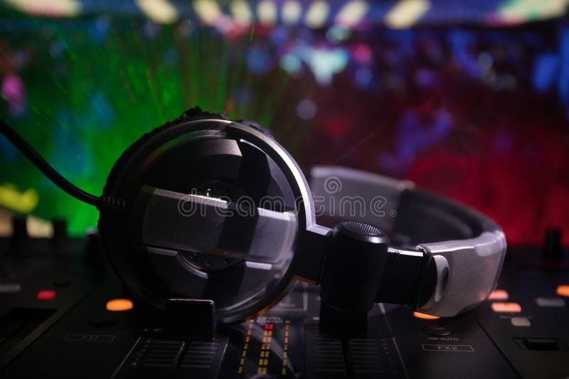 In selective focus of Pro dj controller.The DJ console deejay mixing desk at music party in nightclub with colored disco lights. stock image