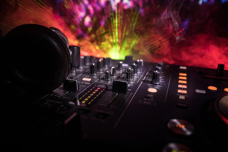 In selective focus of Pro dj controller.The DJ console deejay mixing desk at music party in nightclub with colored disco lights. stock photo