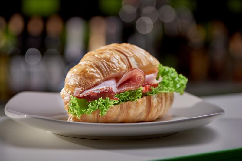 Selective focus of recently prepared tasty croissant in cafe. Selective focus of recently prepared tasty croissant staying on plate at blurred background in cafe royalty free stock photos