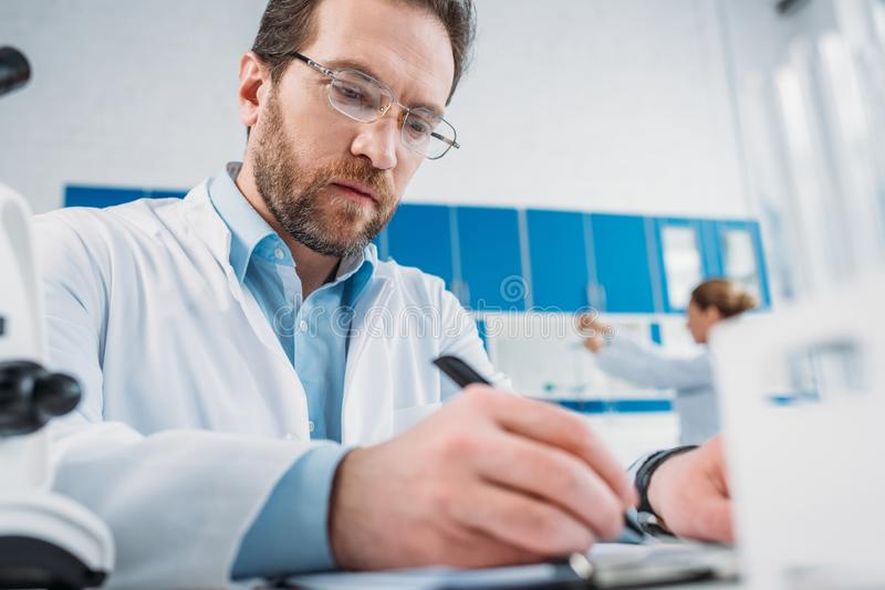 Selective focus of scientist in white coat and eyeglasses making notes in notepad at workplace. In laboratory royalty free stock image