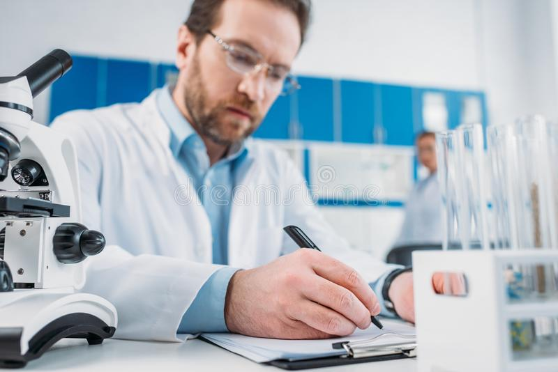 Selective focus of scientist in white coat and eyeglasses making notes in notepad at workplace. In laboratory stock images