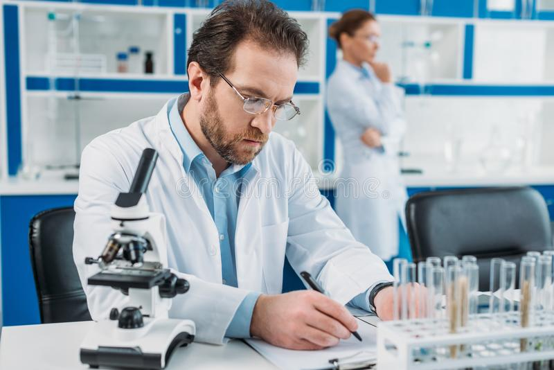 Selective focus of scientist in white coat and eyeglasses making notes in notepad at workplace with microscope. In laboratory stock images