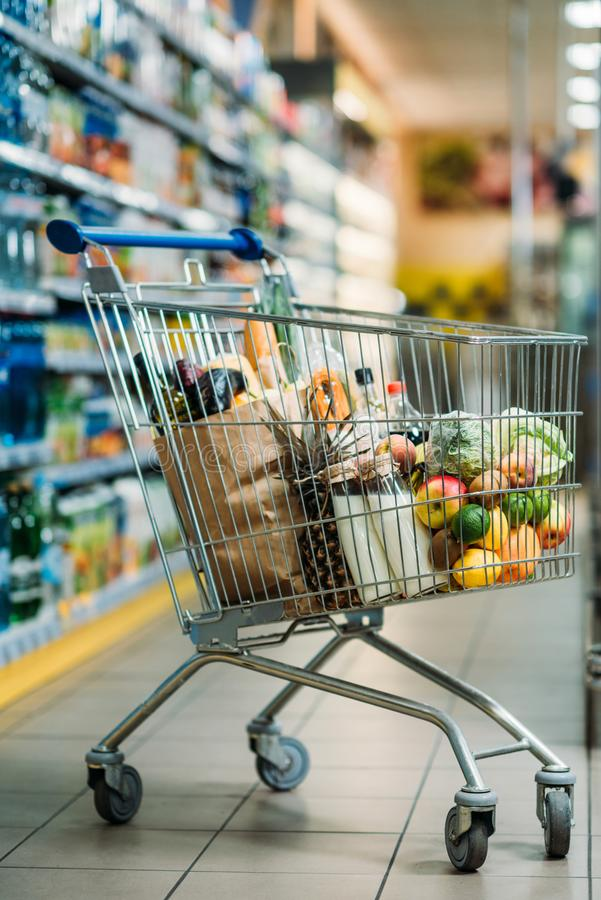 selective focus of shopping cart with purchases royalty free stock images