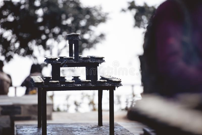 Selective focus shot of a stand with candles and a blurred background at a Hindu temple in Nepal. A selective focus shot of a stand with candles and a blurred royalty free stock photography