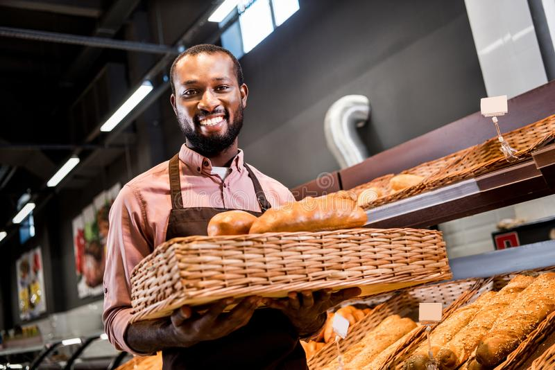 Selective focus of smiling male african american shop assistant in apron holding loaves of bread. In grocery store royalty free stock photo