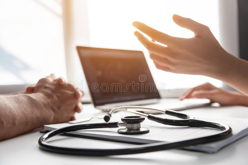 Female Doctor talking with senior man patient. stock photos