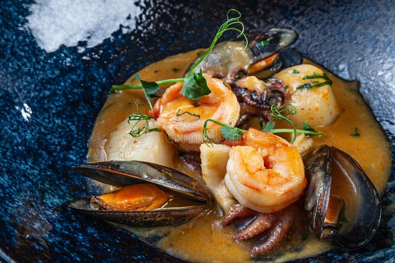 Selective focus on tasty sauteed seafood in a creamy sauce. Shrimp, scallops, mussels, octopus in a dark plate. Close up. Copy stock images