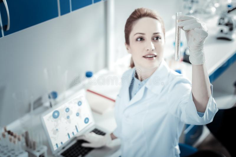 Selective focus of a test tube. Modern lab. Selective focus of a test tube being in hand of nice smart female scientist while working in the lab stock photos
