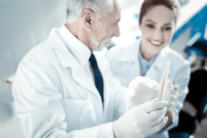 Selective focus of a test tube with a sample. Professional lab. Selective focus if a test tube with a test sample being in hands of a smart delighted royalty free stock image