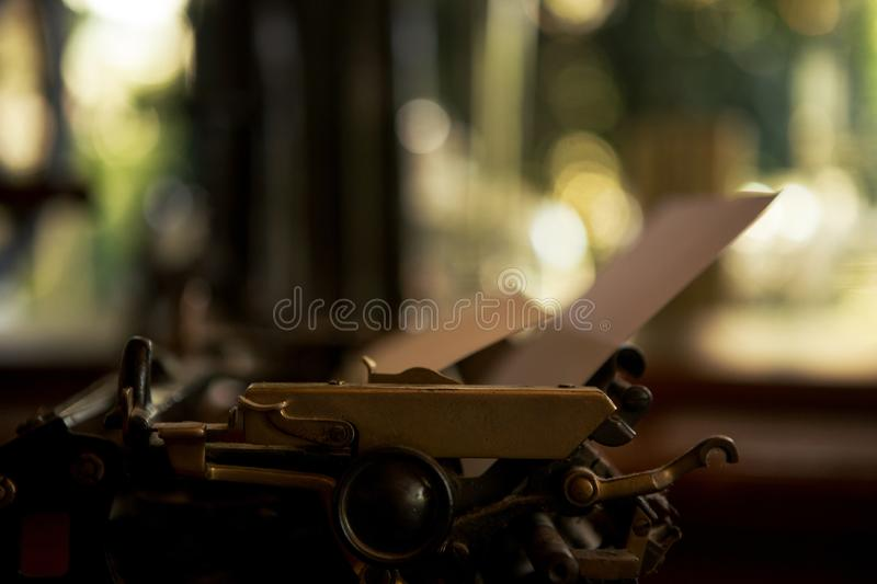 Selective focus on 19th century old black typewriter with blank paper ready for new text. Copy space stock image