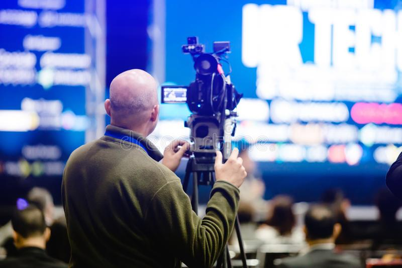 Selective focus to cameraman and video camera set are recording to speaker and audience. In conference hall or seminar event. exhibition convention center. mass stock photos