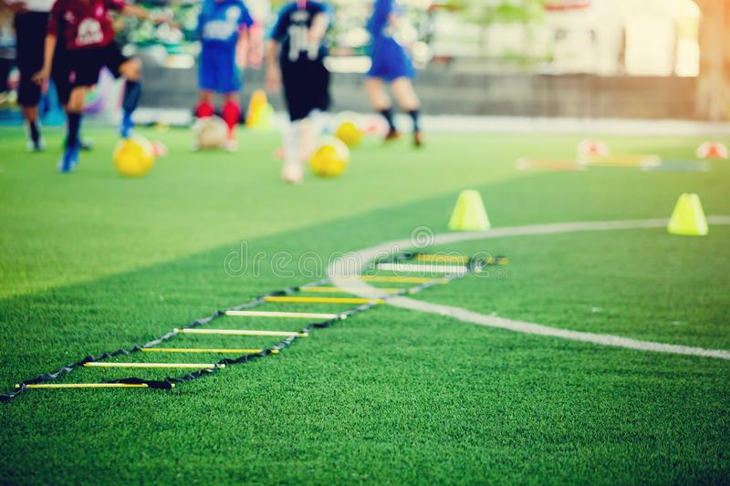 Selective focus to ladder drills on green artificial turf with blurry coach and kid soccer are training. Blurry kid soccer jogging between marker cones and stock photos