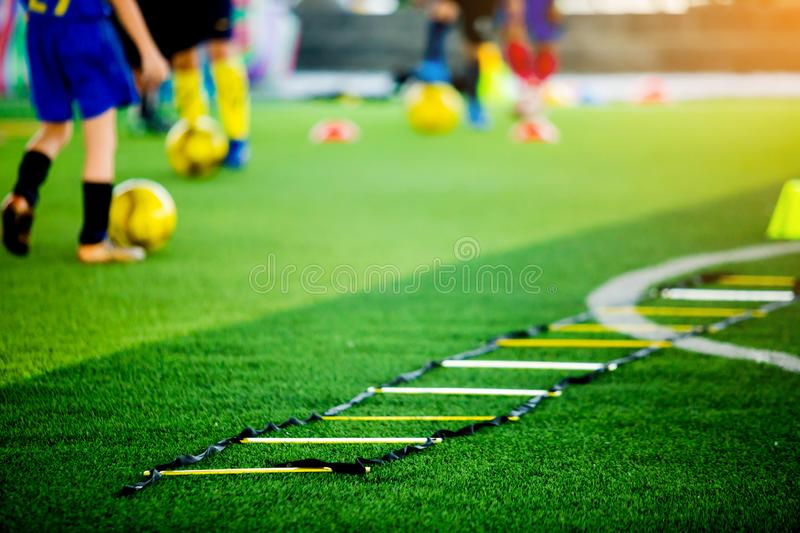 Selective focus to ladder drills on green artificial turf with blurry coach and kid soccer are training. Blurry kid soccer jogging between marker cones and royalty free stock image