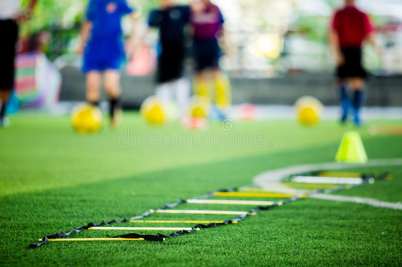 Selective focus to ladder drills on green artificial turf with blurry coach and kid soccer are training. Blurry kid soccer jogging between marker cones and royalty free stock photography