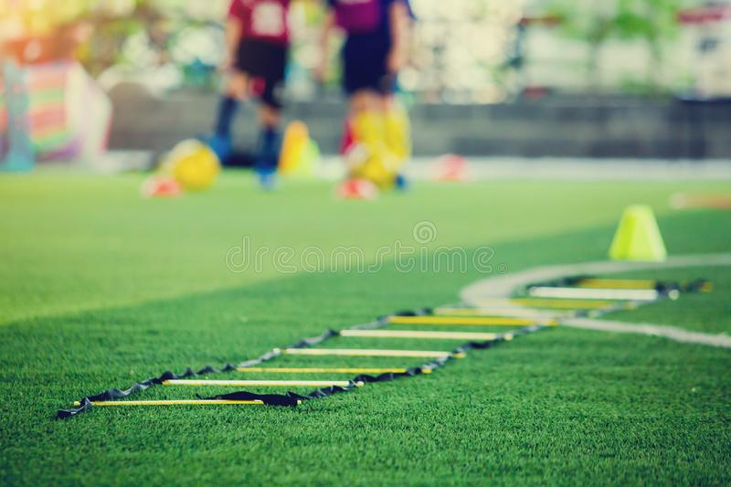 Selective focus to ladder drills on green artificial turf with blurry coach and kid soccer are training. Blurry kid soccer jogging between marker cones and royalty free stock images