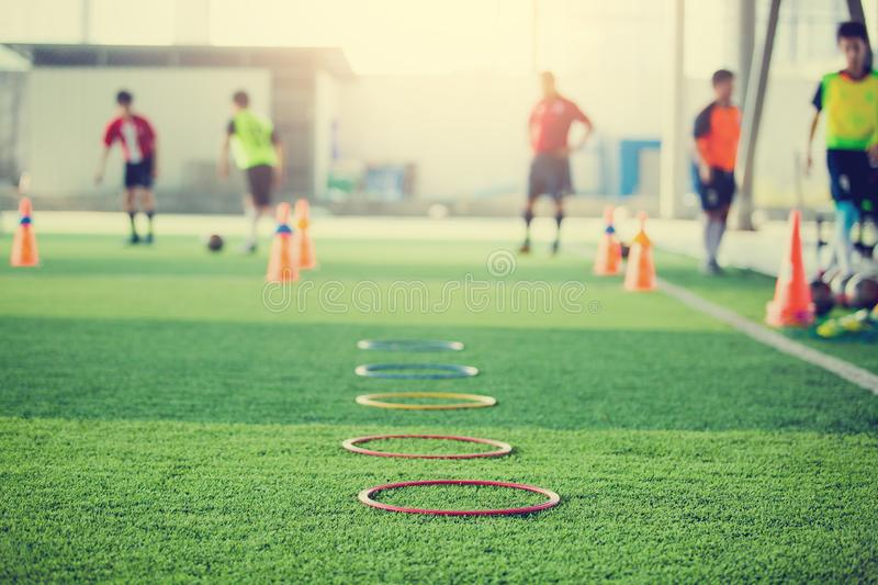 Selective focus to ring ladder marker and cone are soccer training equipment on green artificial turf with blurry kid players. Training background. material for stock image