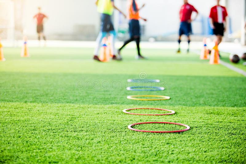 Selective focus to ring ladder marker and cone are soccer training equipment on green artificial turf with blurry kid players. Training background. material for royalty free stock photo