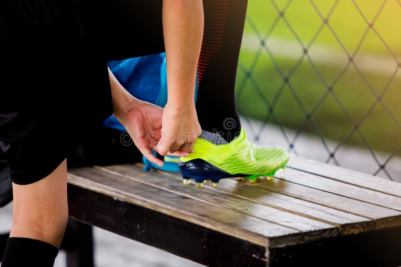 Selective focus to soccer players stand and tying sport shoelaces. Before training football stock photography