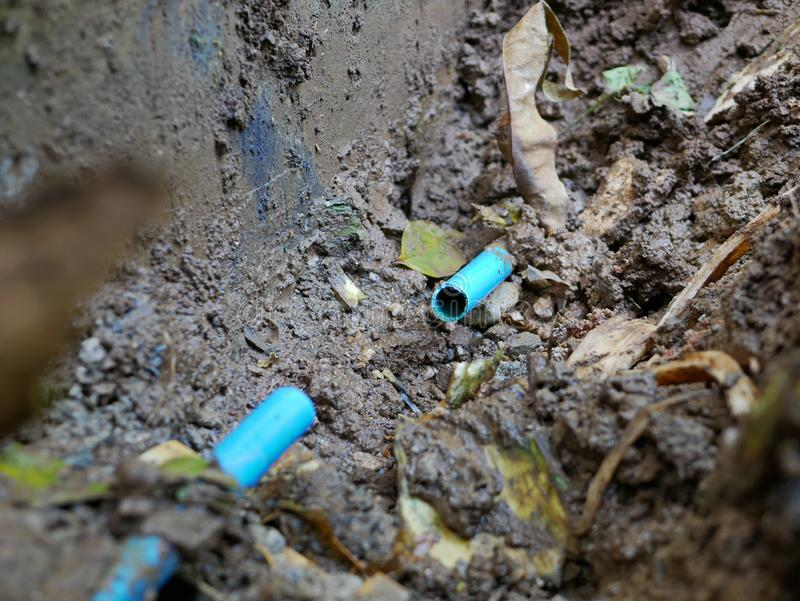 Underground broken / leaked / cracked PVC, polyvinyl chloride, water pipe is partly cut off, getting ready to be fixed. Selective focus of underground broken / royalty free stock photos