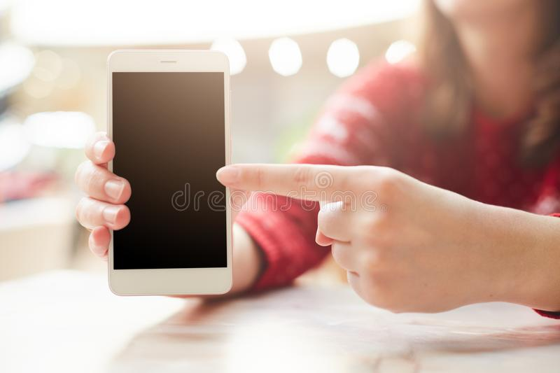 Selective focus. Unrecognizable female keeps modern white smart phone in hand, points with finger at blank copy screen for your te. Xt or information content stock image