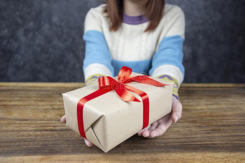 Selective focus of Woman hands holding gift box with red ribbon for Christmas and New Year`s Day or Greeting season royalty free stock images