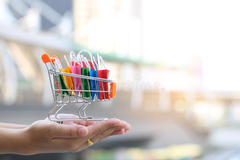 Selective focus of Woman hands holding paper shopping bag on mod royalty free stock image